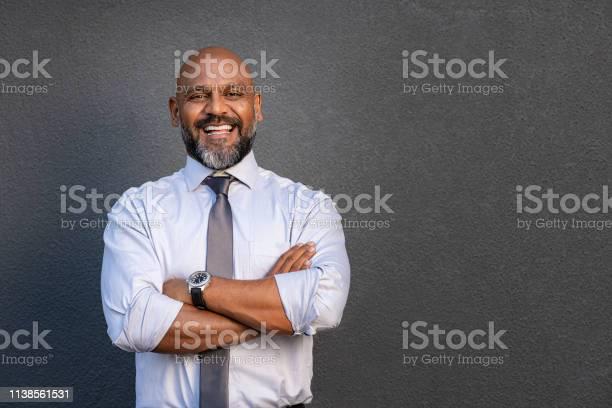 折られる腕と立っている幸せな成熟したビジネスマン - 1人のストックフォトや画像を多数ご用意