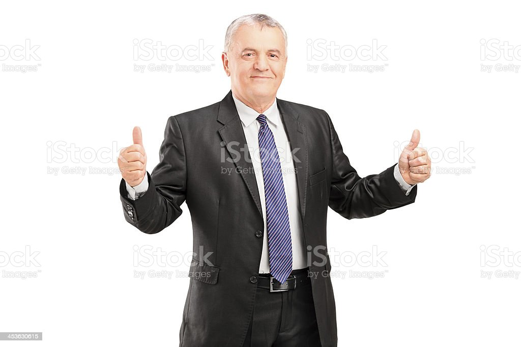 Happy mature businessperson standing and giving thumbs up royalty-free stock photo
