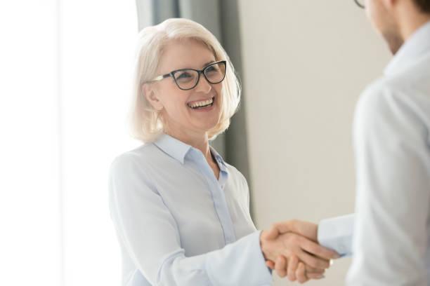 felice matura imprenditrice handshaking partner cliente, fiducia e gratitudine stretta di mano - fedeltà foto e immagini stock