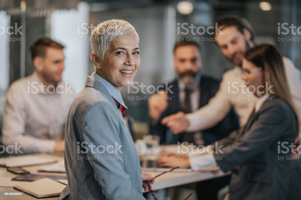 Happy mature businesswoman on a meeting with her colleagues. royalty-free stock photo