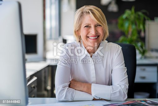 istock Happy mature businesswoman sitting at desk 515444840