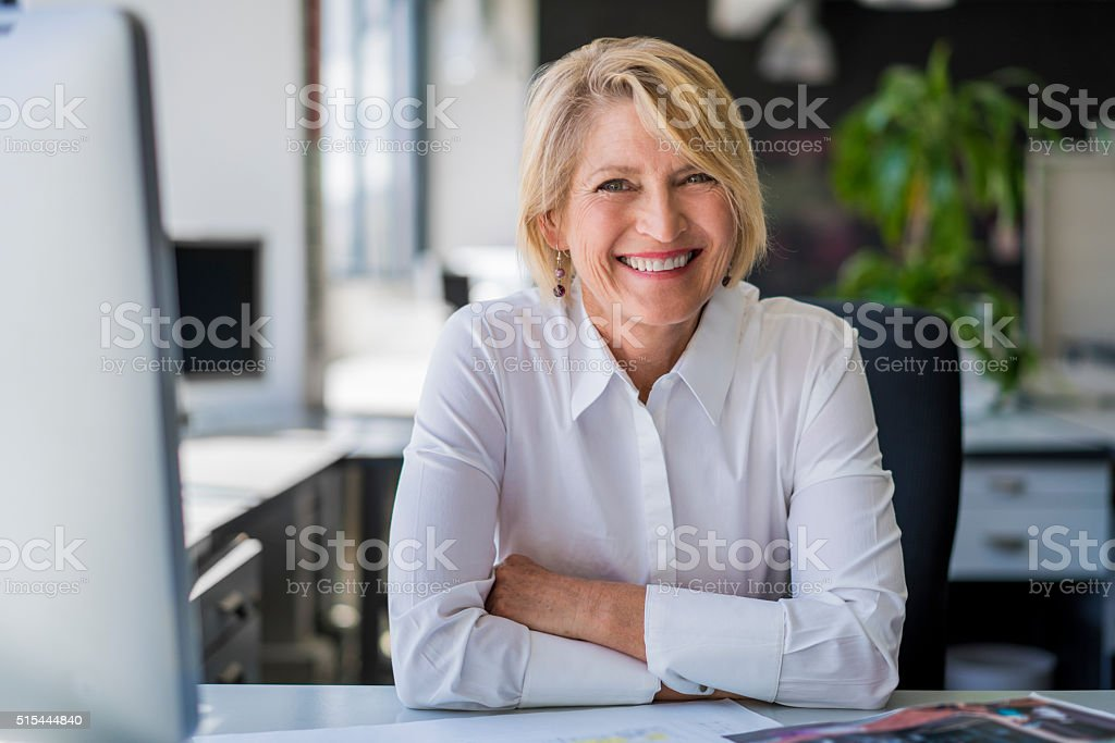 Happy mature businesswoman sitting at desk stock photo