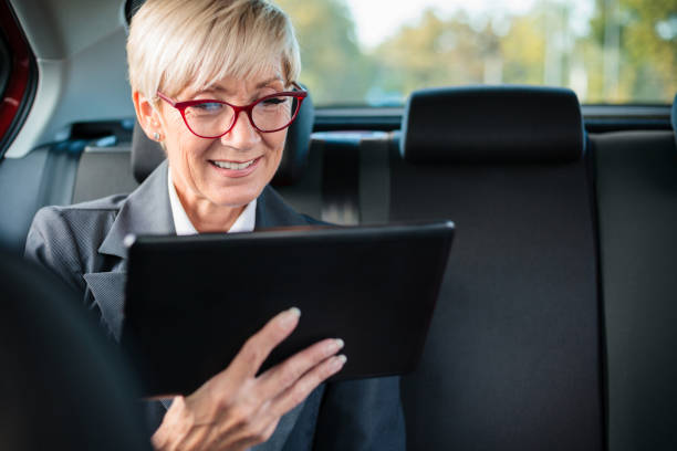 happy mature businesswoman smiling and using tablet on a back seat of the car - senior business woman tablet imagens e fotografias de stock