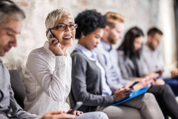 Glücklich Reife geschäftsfrau reden über Handy während des Wartens auf Job-Interview. – Foto