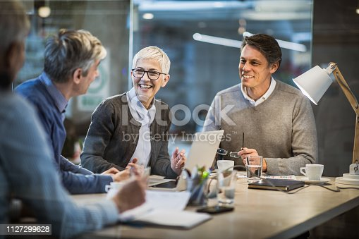 istock Happy mature businesswoman talking to her colleagues on a meeting in the office. 1127299628