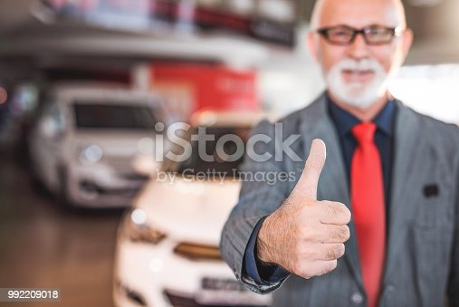 1138561232 istock photo Happy mature car salesman showing thumb up. 992209018