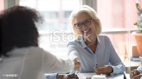 istock Happy mature caucasian leader handshake african employee at group meeting 1146468261