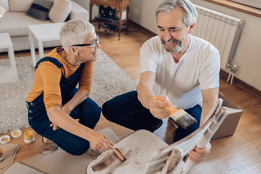 594910248 istock photo Happy mature couple coloring a chair at home 1227153926
