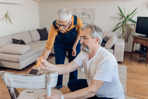 594910248 istock photo Happy mature couple coloring a new chair 1227153924
