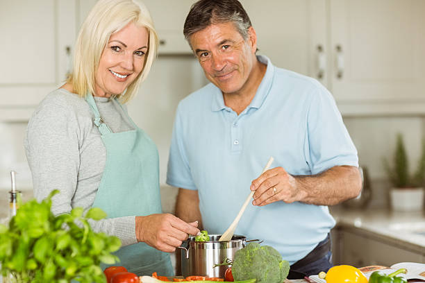 A happy mature couple cooking their dinner together stock photo