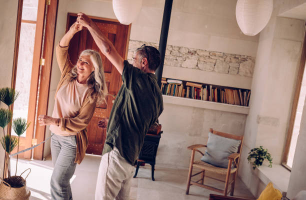 Happy mature couple dancing and celebrating together at home stock photo