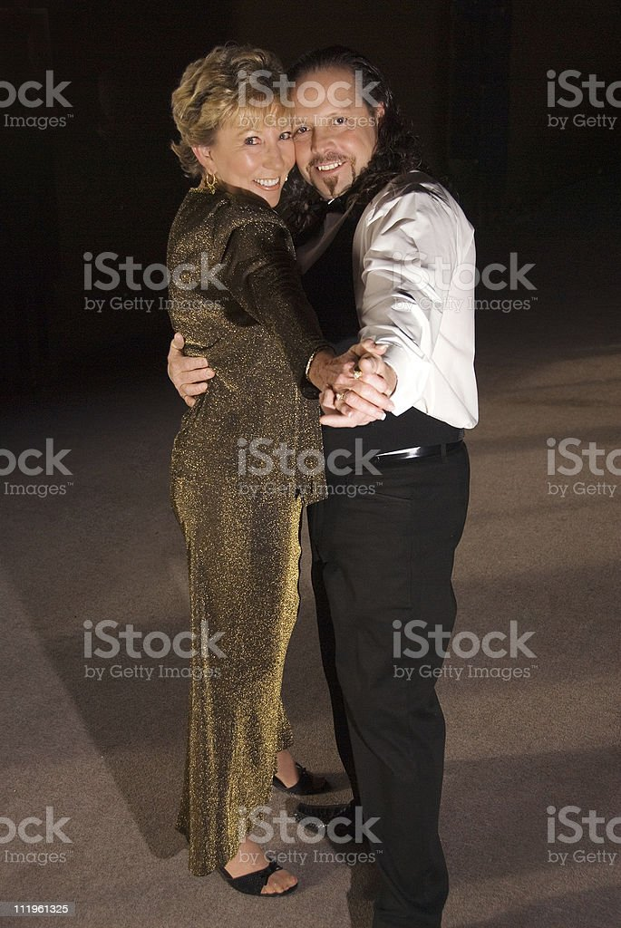 Happy mature couple dancing on a dance floor royalty-free stock photo