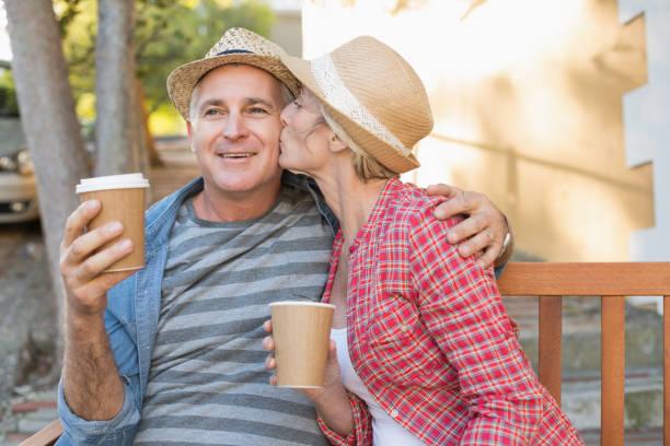 gelukkig ouder paar koffie drinken op een bankje in de stad - 50 59 jaar stockfoto's en -beelden