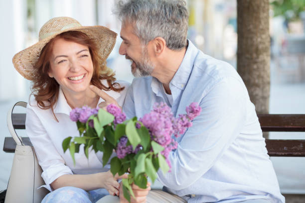 gelukkig ouder echtpaar genieten van hun tijd samen, zittend op een bankje op het dorpsplein - mid volwassen koppel stockfoto's en -beelden