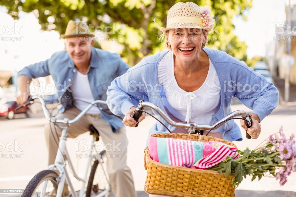 Happy mature couple going for a bike ride in the city stock photo