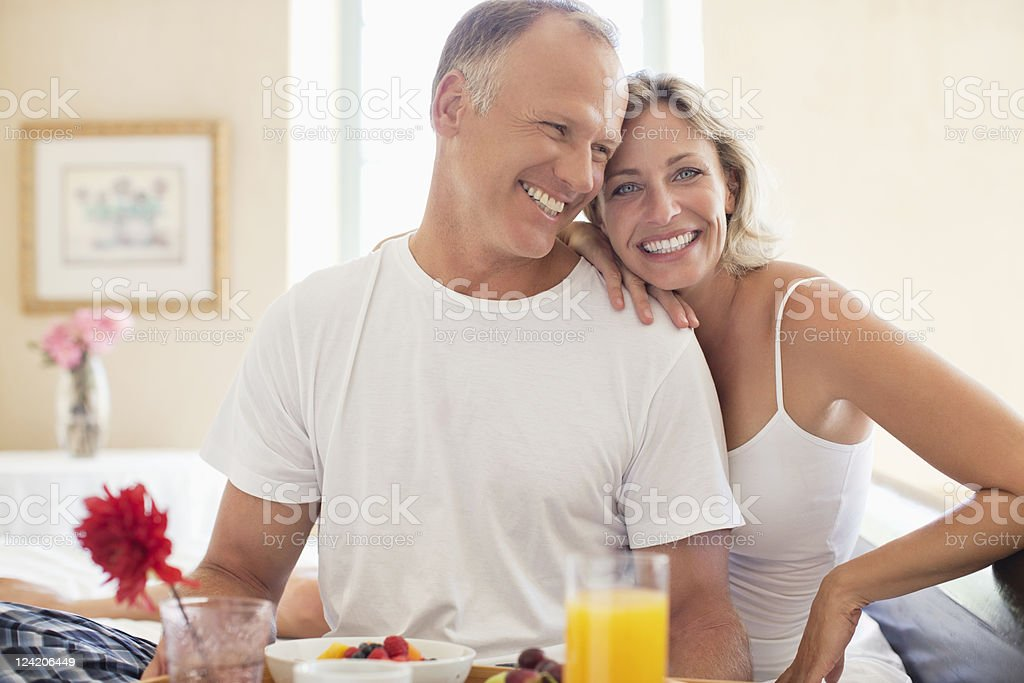 Happy mature couple having breakfast in bed stock photo