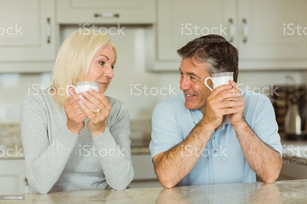 Happy mature couple having coffee together and smiling stock photo