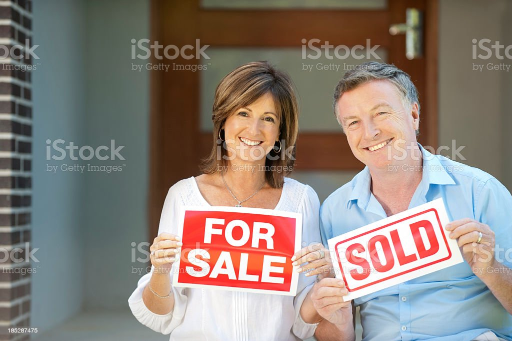 Happy mature couple holding for sale and sold signs stock photo