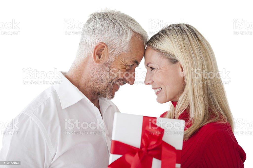 Happy mature couple holding gift stock photo