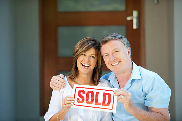 Happy mature couple holding sold sign Happy mature couple holding sold sign in front of a new house buy single word stock pictures, royalty-free photos & images