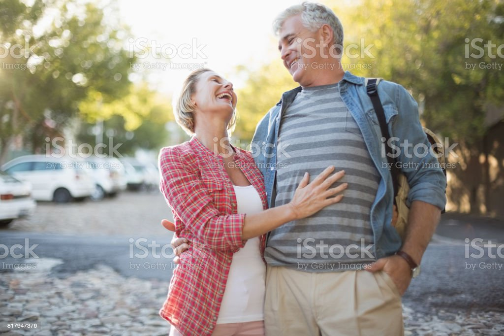 Happy mature couple hugging in the city stock photo