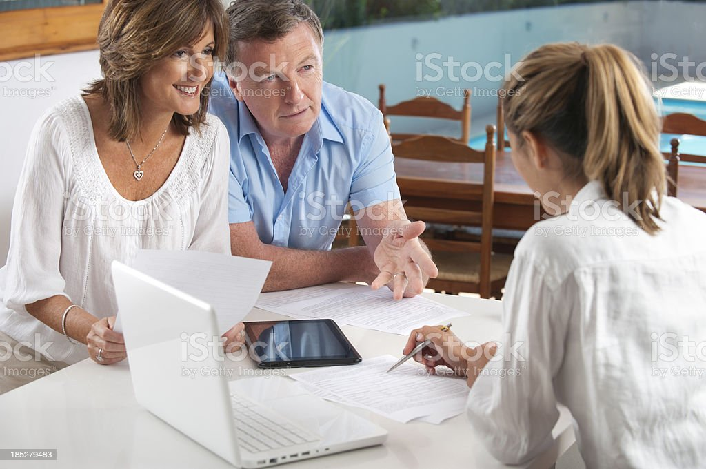 Happy mature couple in a meeting with an adviser stock photo