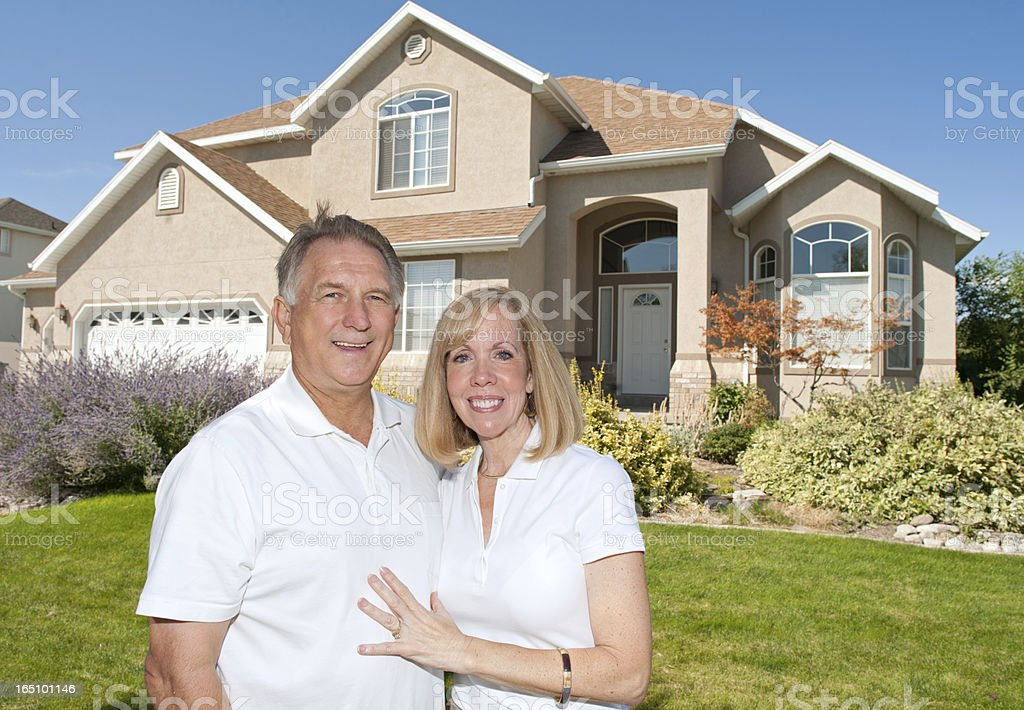 Happy Mature Couple In Front of Nice American Home stock photo