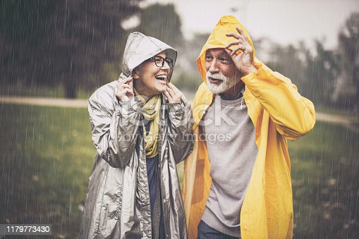 Happy senior couple in raincoats covering their heads during rainy day in nature.