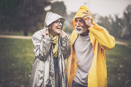 Happy mature couple in raincoats during rain in the park.