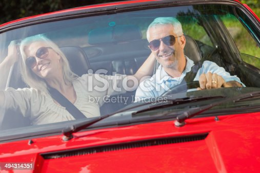 Happy mature couple in red cabriolet going for a ride on sunny day