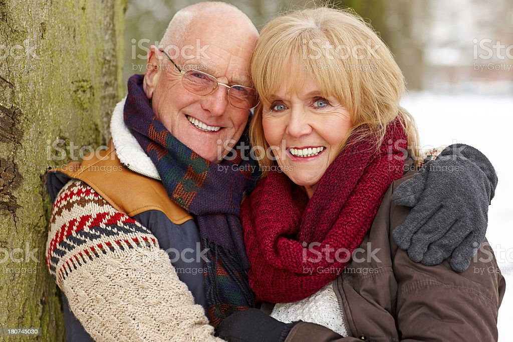 Happy mature couple in winter clothing smiling at camera royalty-free stock photo