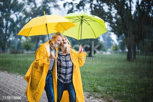 Happy senior couple in raincoats taking a walk under umbrellas on a rainy day at the park.