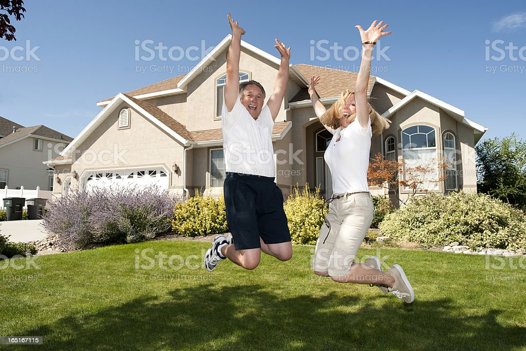 Happy Mature Couple Jumping Outside Home stock photo