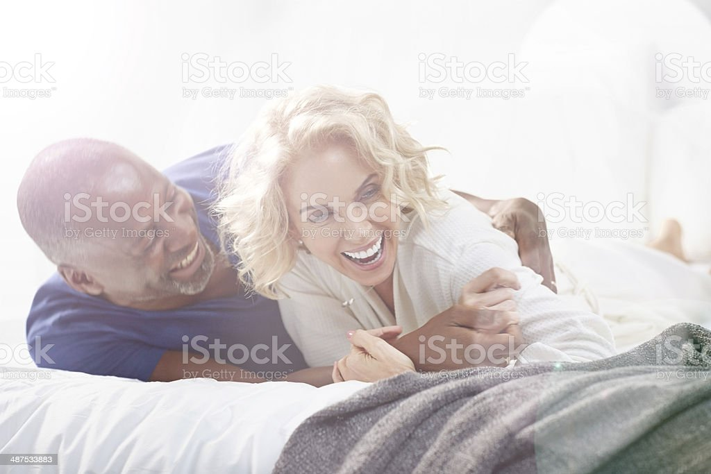 Happy mature couple lying on bed stock photo