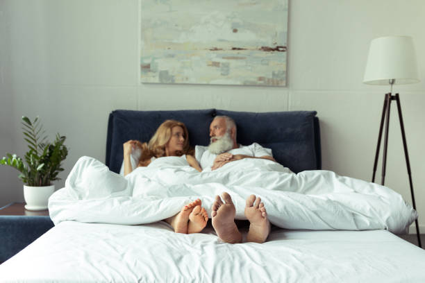 Happy mature couple lying under blanket in bed and smiling each other stock photo