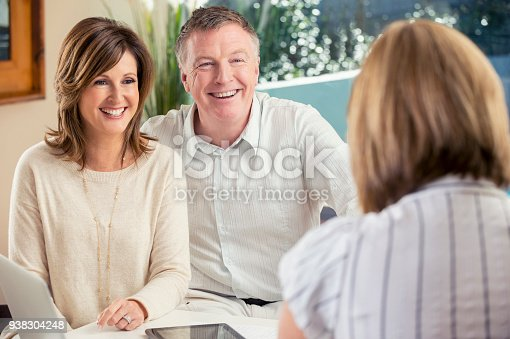 1040654052 istock photo Happy mature couple meeting with advisor at home. 938304248