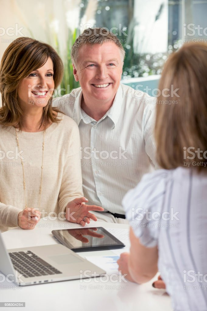 Happy mature couple meeting with advisor at home. stock photo