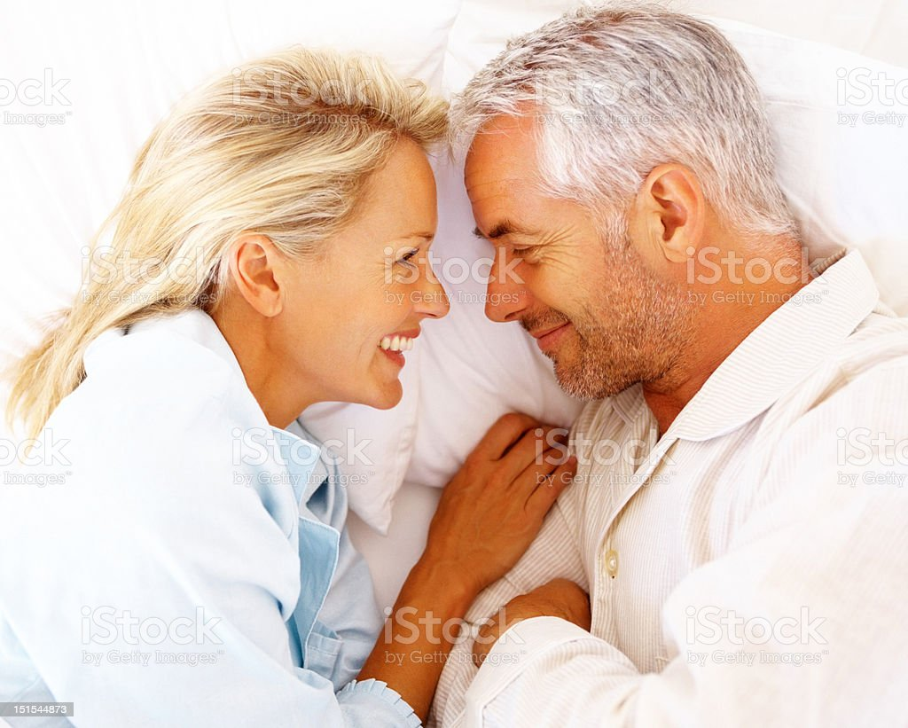 Happy mature couple on bed stock photo