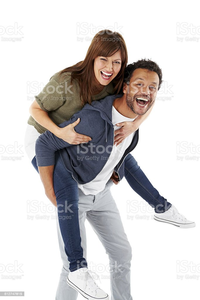 Happy mature couple piggybacking on white stock photo