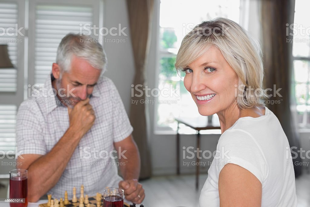 Happy mature couple playing chess at home stock photo