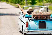 Happy Mature Couple portrait on a Road trip Vacation driving a Vintage car
