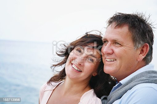 119998253 istock photo A happy mature couple posing in front of the sea  153713956