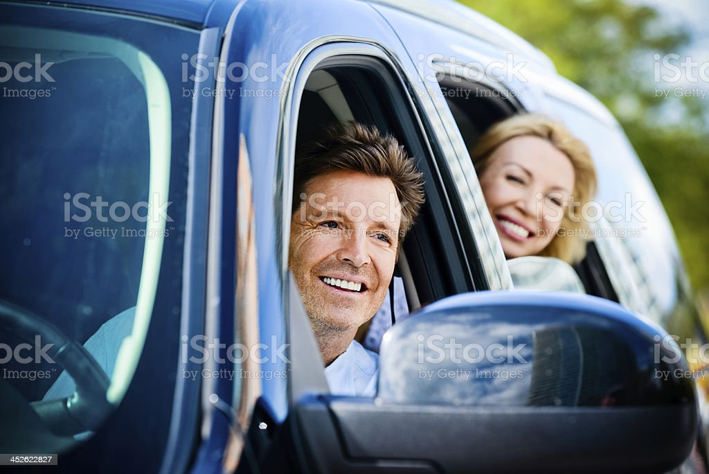 Happy Mature Couple ready to travel in a their car royalty-free stock photo