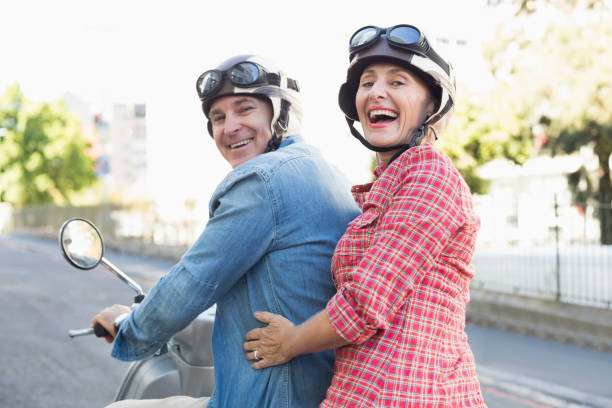 Happy mature couple riding a scooter in the city stock photo