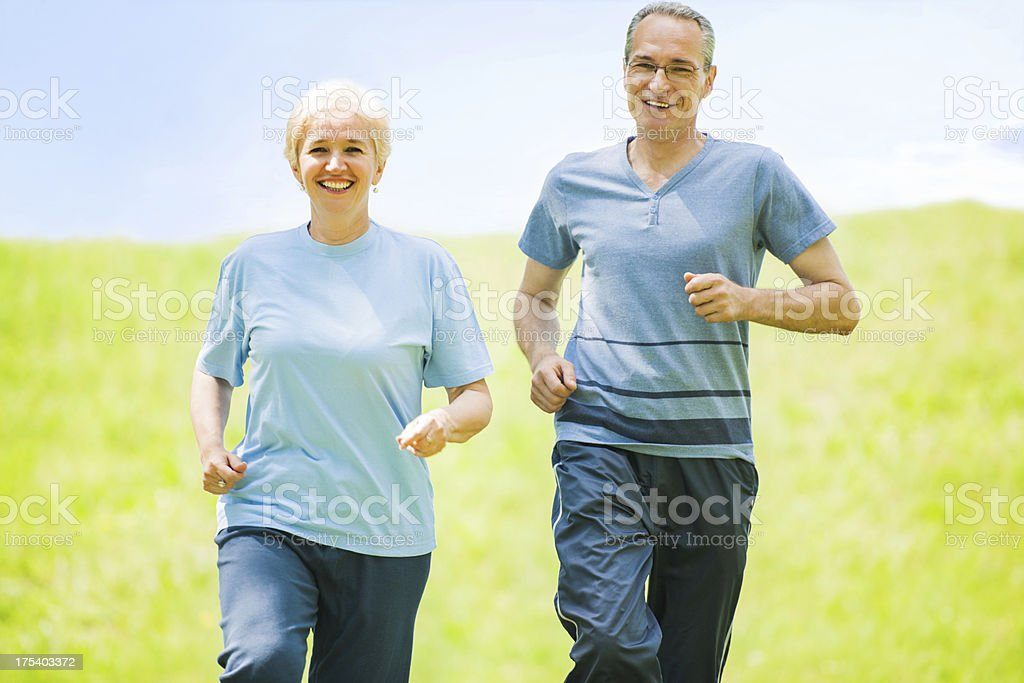 Happy mature couple running in the field. royalty-free stock photo