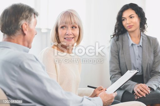584597964 istock photo Happy mature couple signing contract at home 1202683039