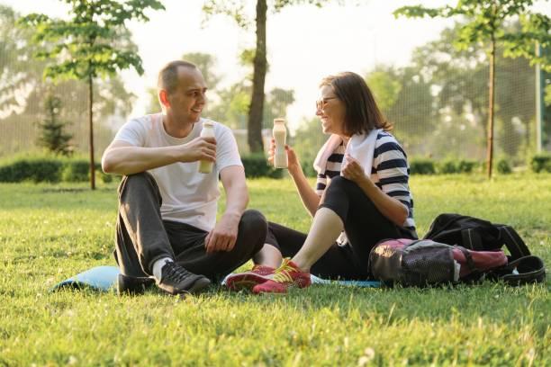 Feliz pareja madura sentado en el parque en estera de fitness, descansando beber yogur después de ejercicios deportivos. - foto de stock