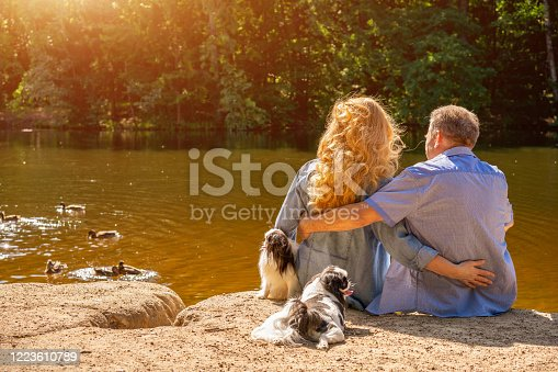 Happy Mature couple sitting on the lake in the sun with their dogs. Concept of family vacation in nature