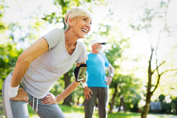 Happy mature couple stretching during running in the park stock photo
