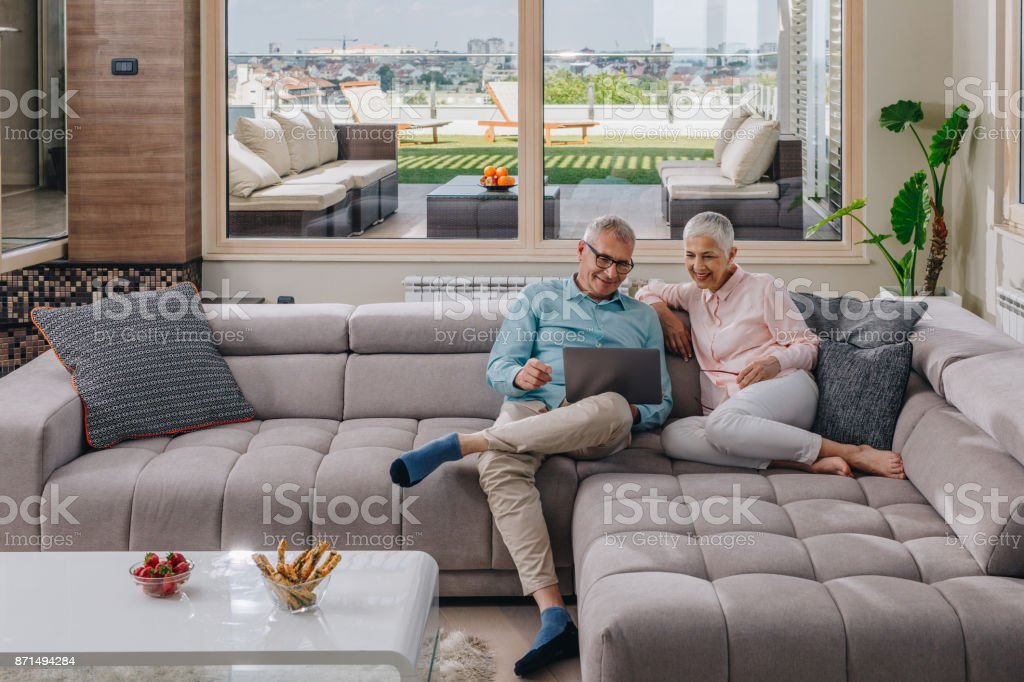 Happy mature couple surfing the Internet on their laptop in the living room. stock photo